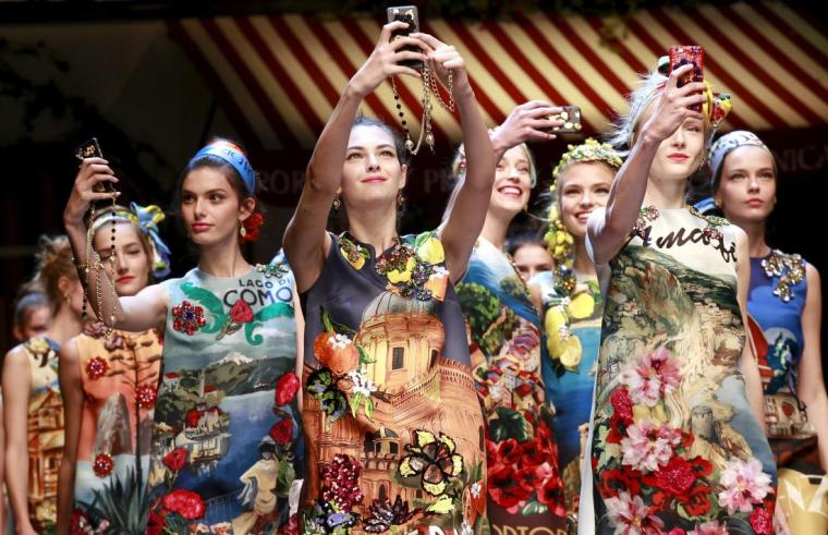 Models take selfie with mobile phones during the parade at the end of the Dolce & Gabbana Spring/Summer 2016 collection during Milan Fashion Week